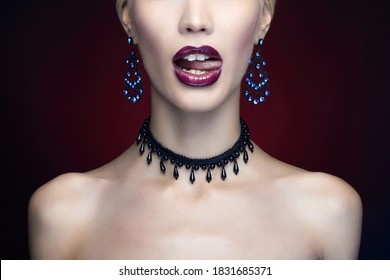 Beautiful girl licking the tongue with shiny lips. Art make-up young woman in necklace