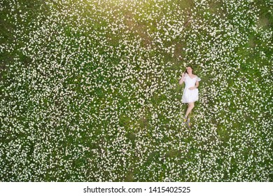 Beautiful girl lies in camomile daisy flower. View from above. Aerial photography.