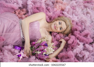 Beautiful girl lies on a background of pink dress. Close-up portrait of a top view.