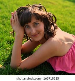 Beautiful girl lies on a green grass