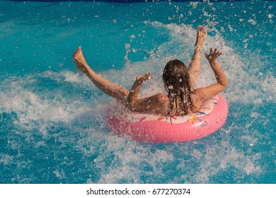 Beautiful girl lies on an inflatable circle in the pool. Spray in the pool