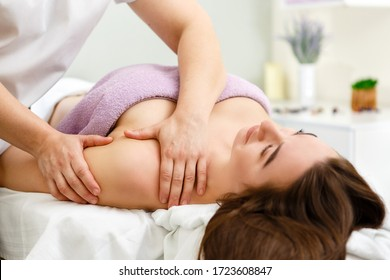 A beautiful girl lies on a massage table and she gets a massage that she enjoys in the massage room