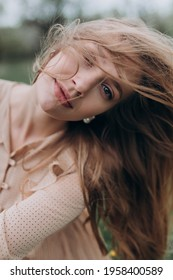 a beautiful girl with light brown hair in a beige dress in a blooming apple orchard her hair fluttering in the wind