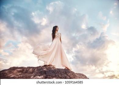 Beautiful girl in a light summer dress beige walks in the mountains. Light dress flutters in the wind, blue summer sky. Fabulous spring landscape, brunette walks in crater of volcano