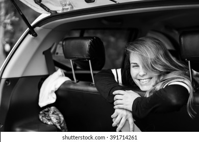 beautiful girl , like a cheerleader . Attractive girl sitting in a car and smiling . pretty girl traveling in a car with friends.