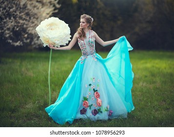 A beautiful girl like Thumbelina in a blue fluffy dress near a giant peony flower. Blonde with huge fairy flowers. As from a fairy tale.