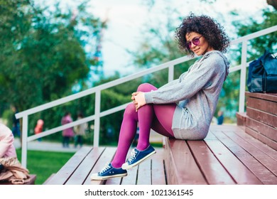 a beautiful girl in lilac glasses, with an afro hairdo, smiling and laughing, in a park on a skateboard, with green grass scimecks in philosopher's leggings and a gray blouse