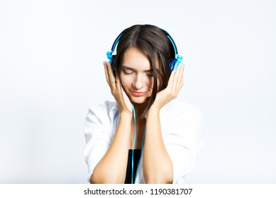 beautiful girl listening to music in big headphones, short haircut, isolated over a white background