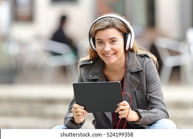 Beautiful girl listening music with headphones and tablet looking at you sitting in a bench in the street