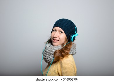 beautiful girl listening to music on headphones in a bright yellow color, lifestyle winter clothes isolated on a gray background