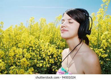 A beautiful girl listening music on a field of spring canola flowers.