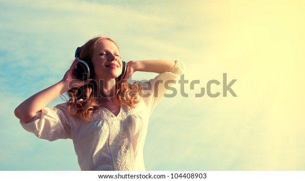 beautiful girl listening to music on headphones in the sky