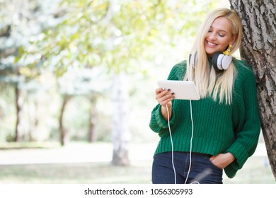 Beautiful girl listening to music in the park.