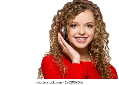 Beautiful girl listening to music in red headphones. Isolate. Portrait of a girl with orthodontic appliance.
