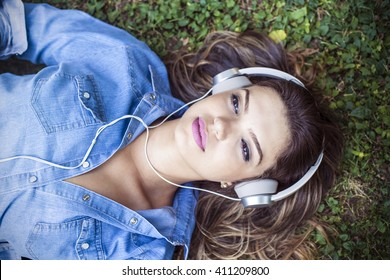 Beautiful girl listens to music on the grass