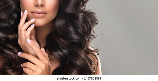 Beautiful girl with long black wavy hair   and  pearl manicure .  Woman  with light coloured nails . Makeup and cosmetics
