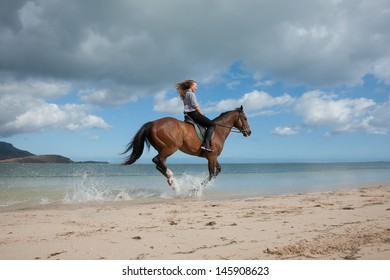 beautiful girl with long blond hair riding on a brown horse on the shore of Indian Ocean on the island of Mauritius