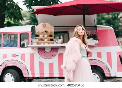 Beautiful girl with long blonde hair in tulle skirt on  retro coffee car background. She wears pink fur coat on shoulder, looks to camera