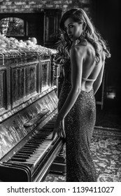 Beautiful girl in long classic dress posing with old piano. Black-white portrait.