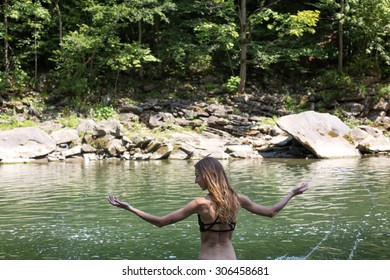 beautiful girl with long curly blonde hair standing by the mountain river waterfall forest during her summer vacation back view