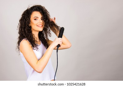 beautiful girl with long curly hair and hair iron straightener isolated studio on white