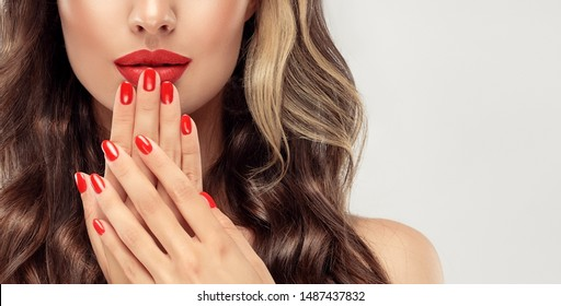 Beautiful girl  long , curly hair . Model woman showing a red   manicure on nails   . Cosmetics and makeup