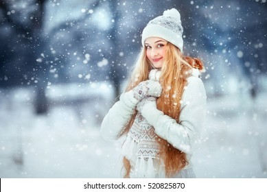 Beautiful girl with long curly hair in  white knitted scarf and hat having fun outdoor in winter forest under snowflakes. Pretty young model standing  on blue background and looking at camera.