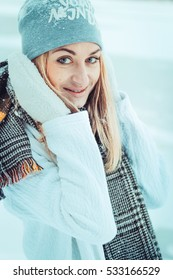 Beautiful girl with long curly hair in white knitted scarf and hat having fun outdoor.Pretty young model standing on snow background and looking at camera.