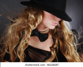 The beautiful girl with long curly hair in a black hat