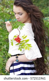 Beautiful girl with long dark hair, his head bowed over a branch of mountain ash