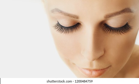 Beautiful girl with long false eyelashes and perfect skin. Eyelash extensions, cosmetology, beauty and skin care. Close up, macro with copy space