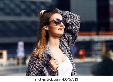 Beautiful girl with long hair in a cardigan, white shirt and sunglasses smile and look up on the background of the business center