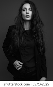 beautiful girl with long hair in a classic black suit and shirt posing. black and white image