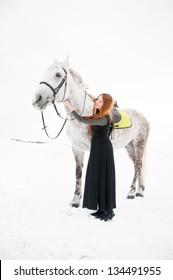 Beautiful girl with long hair embraces a white horse