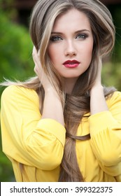 Beautiful girl with long hair. Fashion woman in summer park