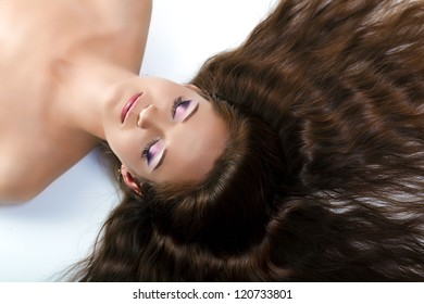 beautiful girl with long hair and make-up with closed eyes lying on the floor