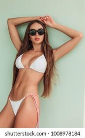 beautiful girl with long hair posing in stylish bikini and sunglasses