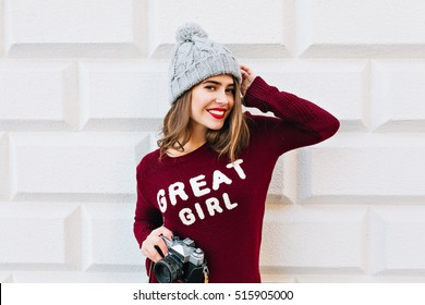 Beautiful girl with long hair and red lips in marsala sweater on grey wall background. She wears knitted hat, holds camer ain hands  and smiling