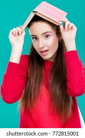 beautiful girl with long hair in red sweater reads book