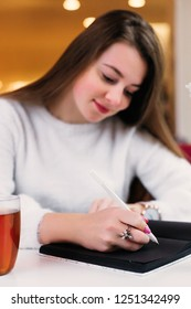 a beautiful girl with long hair sitting in a cafe and writing something in a notebook with black pages