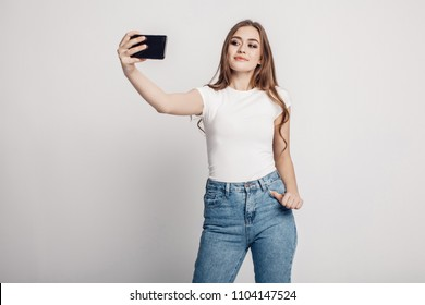 a beautiful girl with long hair in a white t-shirt and blue jeans takes a selfie. white background. suitable for mockup