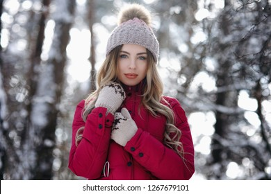 Beautiful girl with long hair in white knitted hat having fun outdoor in winter forest under snowflakes. Pretty young model standing on forest background and looking at camera. - Image