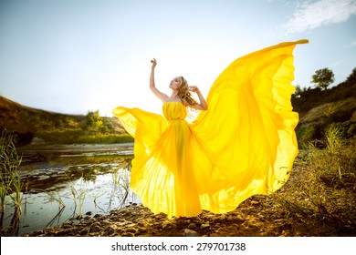 the beautiful girl with long hair in the yellow fluttering dress costs on the bank of a stream, hands raised up, having closed eyes