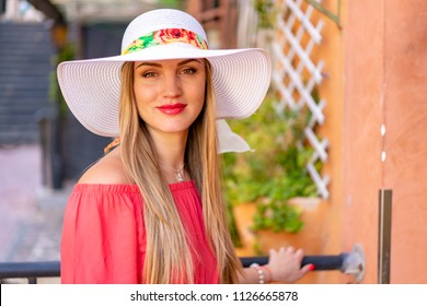 Beautiful girl in a long red dress and a white hat exploring Malta island
