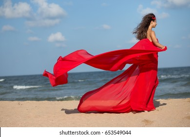 Beautiful girl in a long red dress, that flutters in the wind. Concept of femininity, harmony.
