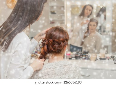 Beautiful girl with long red-hair,  hairdresser weaves a  braid  in a beauty salon on the background of snowflakes. Professional hair care and creating hairstyles.