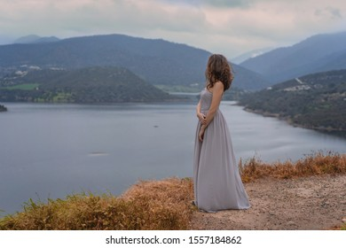 Beautiful girl in long romantic grey dress look on the Scenic landscape Germasogeia reservoir large artificial lake staying on dam during a sunset under dramatic cloudy sky, Limassol district, Cyprus
