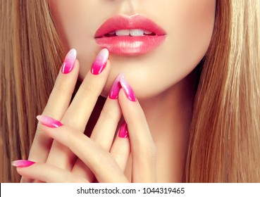 Beautiful girl  long and  straight hair . Model woman showing a pink  manicure french on nails and lips  .