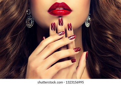 Beautiful girl  long , thick curly hair . Model showing a red   manicure on nails with design  and lips  .