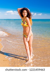 Beautiful girl with long thick dark hair resting on the beach a summer day
